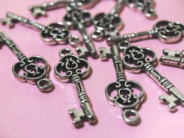 분홍색 배경에 열쇠 형태의 펜던트가 많이 있습니다. 보석을 만들기 위한 재료입니다. 손으로 만든 개념입니다.