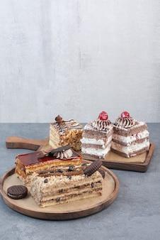 나무 절단 보드에 쿠키와 케이크의 많은 조각.