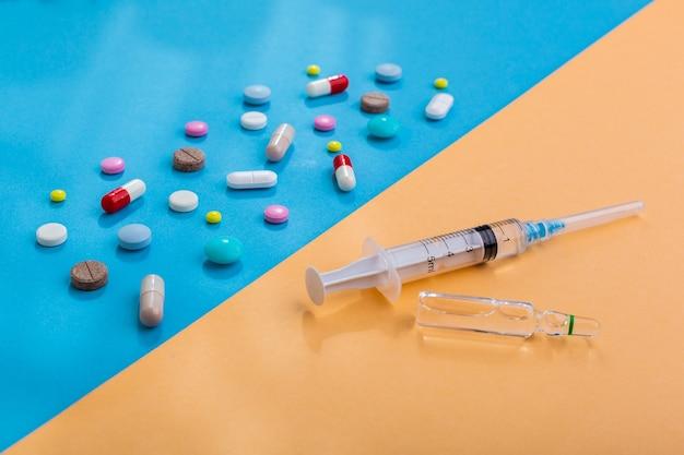 백신에 대한 선택 항생제의 상징으로 주사가 있는 많은 알약과 주사기