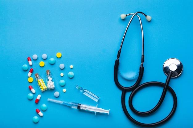 청진기가 있는 파란색 배경에 주사가 있는 많은 알약과 주사기