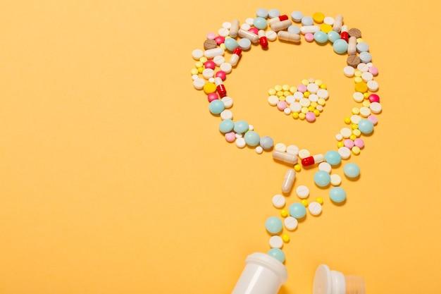 치료의 상징으로 심장 모양의 주황색 배경에 많은 알약