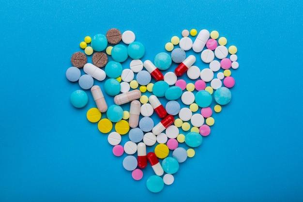 치료의 상징으로 심장 모양의 파란색 배경에 많은 알약