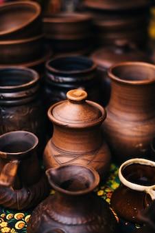 Много керамики на ярмарке. керамическая национальная русская посуда. обожженная черная керамика. обожженные глиняные горшки и тарелки, посуда