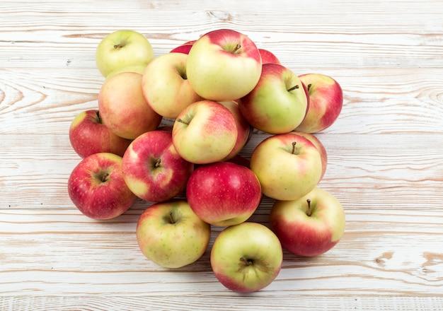 ジュースの準備ができているたくさんの赤と緑の柔らかいリンゴが上面図を生成します。木製の素朴な表面に山積みされた有機リンゴの3キログラム