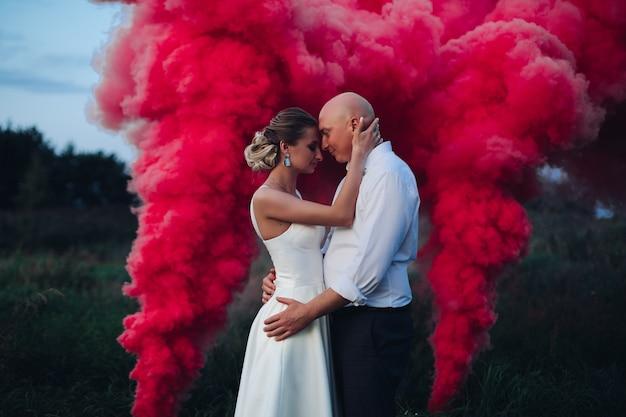 白いドレスと白いシャツと黒いズボンの白人男性の美しい女性の近くにたくさんの赤い煙