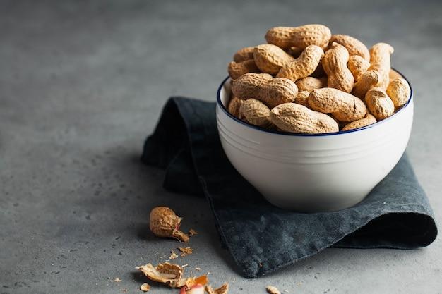 Много жареного арахиса в скорлупе в миске на серой поверхности
