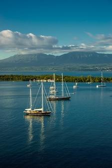 Много парусников в спокойной воде с горами и облаками на поверхности в гваделупе.