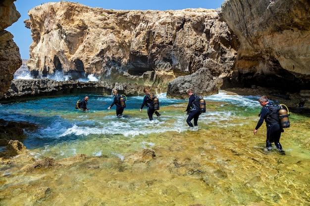 機器内の多くのスキューバダイバーが、日当たりの良い小さな峡谷の青い純粋な水に入っています