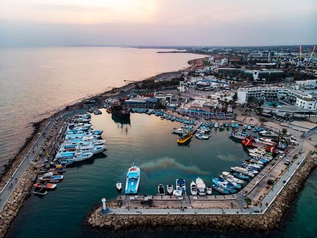 美しい夕日を背景に、海岸近くの港にはたくさんの船が停泊しています。キプロスの地中海沿岸、アギアナパ。