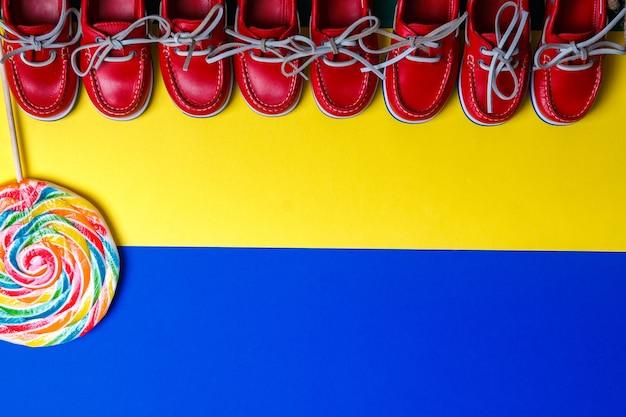 色付きの背景に大きなマルチカラーロリポップの近くの小さな赤いボートシューズがたくさん。トップビュー、コピースペース。フラットレイ