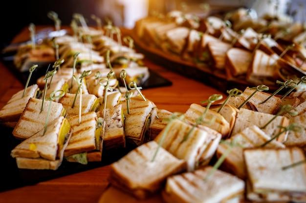 Много закусок и бутербродов на кейтеринге.