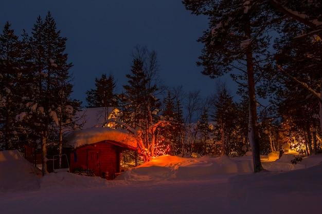 저녁 겨울 숲에 눈이 많이. 나무에 조명과 화환이 있는 집