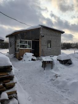 집과 건물의 지붕에 많은 눈이 있습니다. 나라와 도시의 겨울. 반구 곡선의 눈에 태양이 비추고 겨울 집 지붕의 눈이 두껍고,