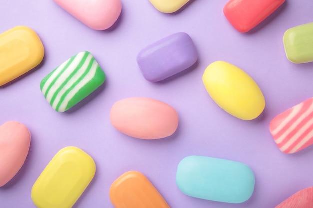 Много твердого мыла для гигиены и чистоты. на фиолетовом столе разбросаны разноцветное мыло и его остатки.