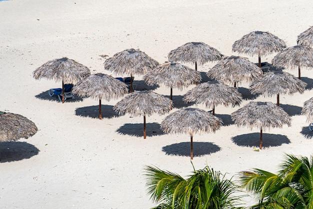 たくさんのわら傘が一列に並び、サンラウンジャーが青い曇り空を背景に白い砂浜に立っています。キューバ、マタンサス州バラデロ