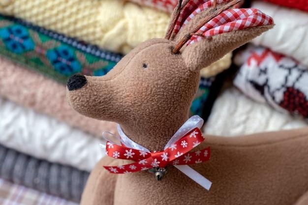 2つの山と鹿のおもちゃに折りたたまれたたくさんのセーターとプルオーバーの異なる色。