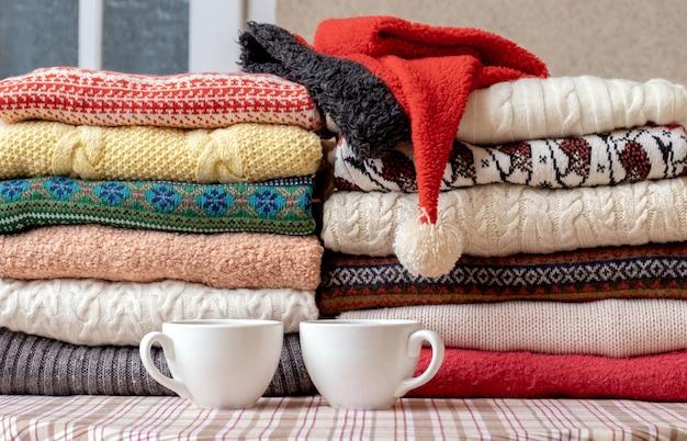 Множество свитеров и пуловеров разных цветов, сложенных в две стопки на столе с двумя чашками кофе.