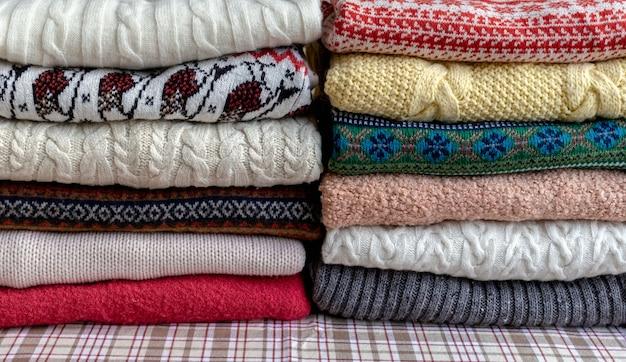 テーブルの上の2つの山に折りたたまれたたくさんのセーターとプルオーバーの異なる色。