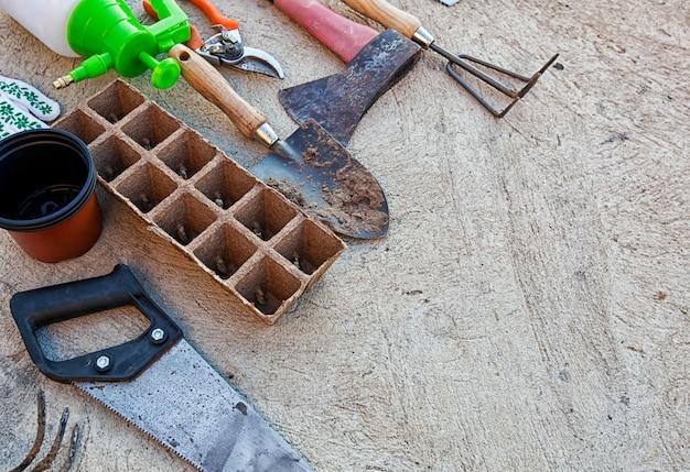 屋外のコンクリートの床に多くの使用済みで汚れたガーデンツール