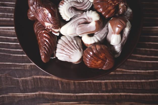 Много разнообразных шоколадных конфет в тарелке