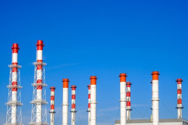 Множество белых и красных промышленных труб на безоблачном голубом небе в солнечный день.