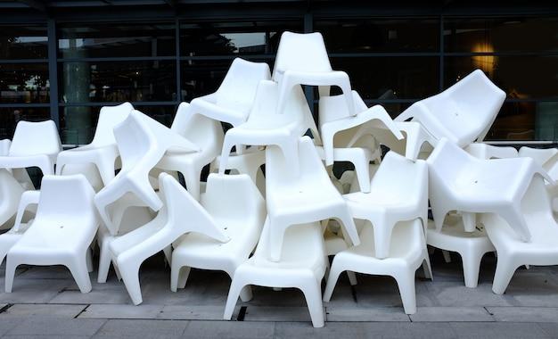 Много белых пластиковых стульев, расположенных в куче.