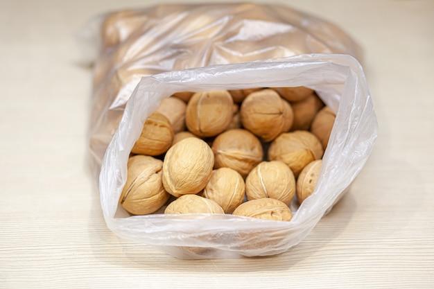 흰색 배경에 가방에 전체 호두를 많이. 단백질과 단백질 함량이 높은 건강한 유기농 식품.