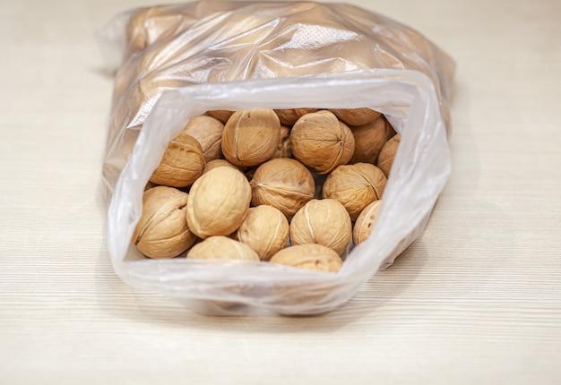 Много целых грецких орехов в сумке на белом фоне. здоровая, экологически чистая пища с высоким содержанием протеина и протеина.