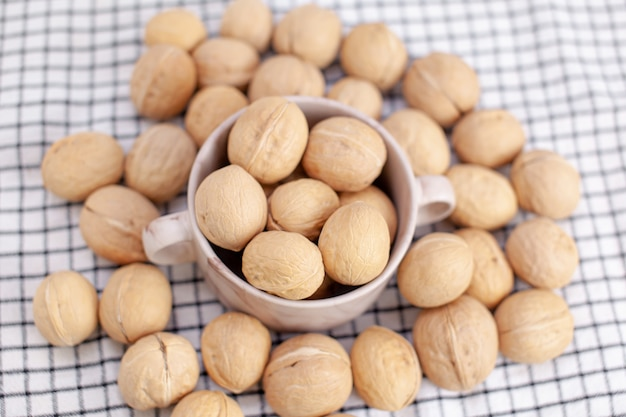 Много целых грецких орехов в чашке на салфетке крупным планом. здоровая, органическая и здоровая пища с высоким содержанием протеина и протеина.