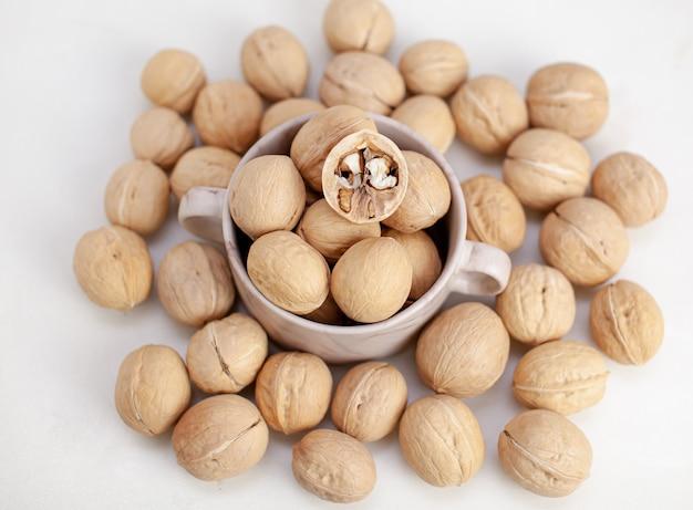 Много целых грецких орехов в чашке на белом фоне крупным планом. здоровая, экологически чистая пища с высоким содержанием протеина и протеина.