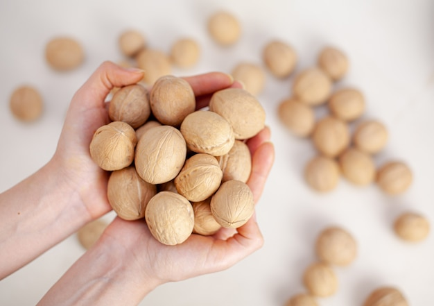흰색 배경 클로즈업에 여성의 손에 전체 호두가 많이 있습니다. 단백질과 단백질 함량이 높은 건강한 유기농 식품.
