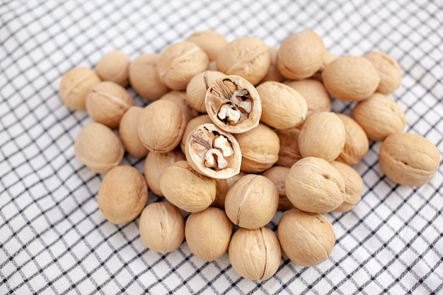 Много целых грецких орехов на салфетке крупным планом. здоровая, органическая и здоровая пища с высоким содержанием протеина и протеина.