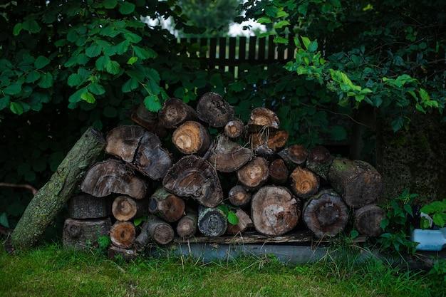 На заднем дворе дома в деревне много дров и бревен.