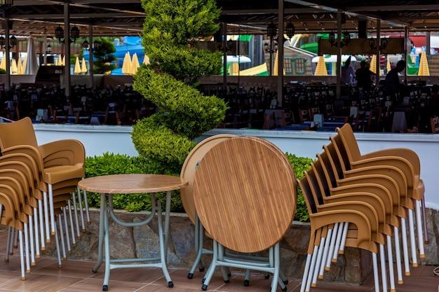 여름 화창한 날에 녹색 울타리 앞에 서 있는 많은 나무 테이블과 의자.