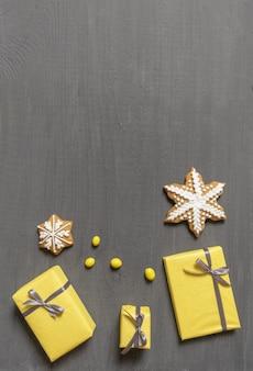 Много желтых подарочных коробок на сером деревянном