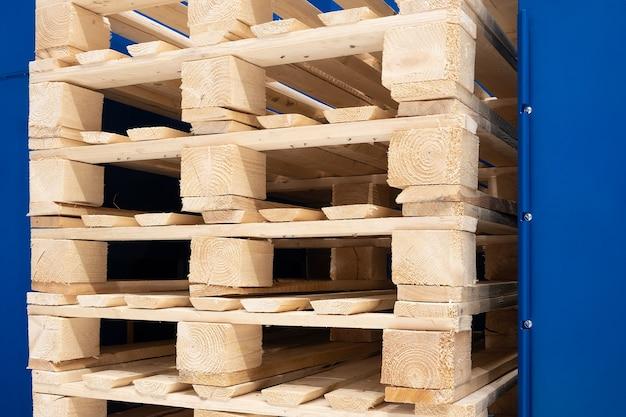 Много штабелей старых деревянных поддонов евро на складе готовы к вторичной переработке. промышленный фон. крупный план.