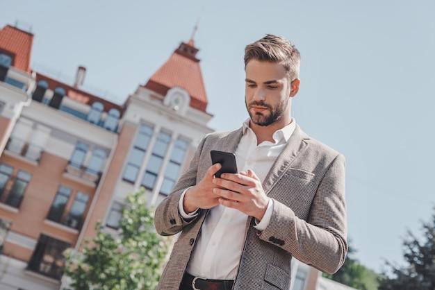 할 일이 많은 심각한 갈색 머리 남자가 서 있는 동안 휴대전화를 보고 있다