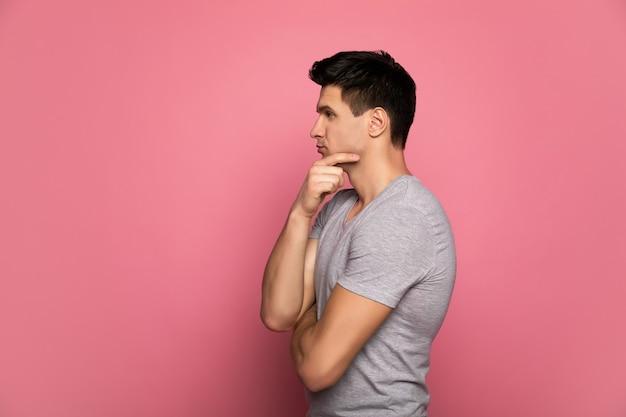 생각할 것이 많습니다. 회색 티셔츠를 입은 매력적인 남자, 프로필에 서서 무언가를 생각하고 오른손으로 턱을 만지고 있습니다.
