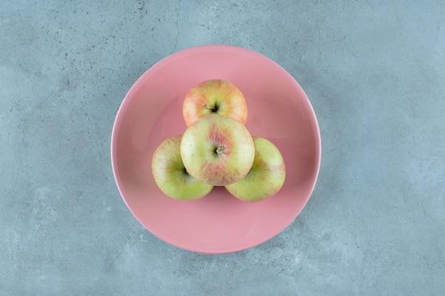 대리석 배경에 접시에 많은 사과.