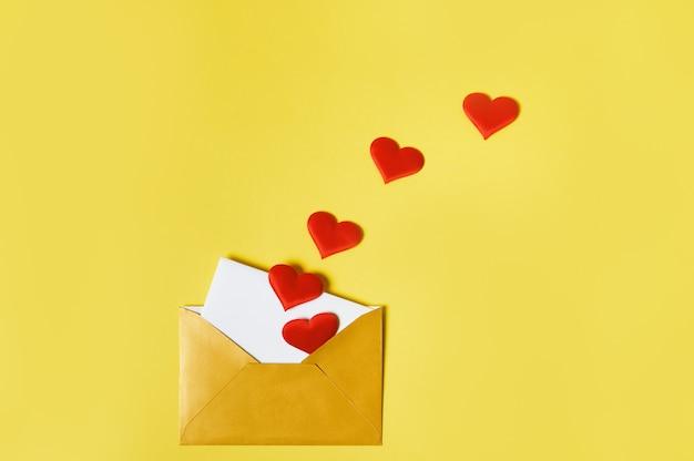 Любовное письмо. раскрытый золотой конверт с сердечками и любовным письмом внутри. день святого валентина концепция.