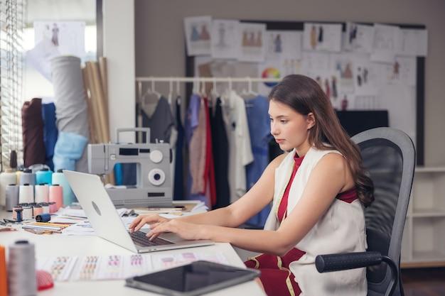 Симпатичная азиатская модельер сидит за своим рабочим столом в своей студии, смотрит в веб-камеру и разговаривает по видеосвязи.