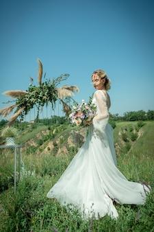 素敵な花嫁、美しい高価なドレスを着た金髪、自然と美しい風景の中を歩いています