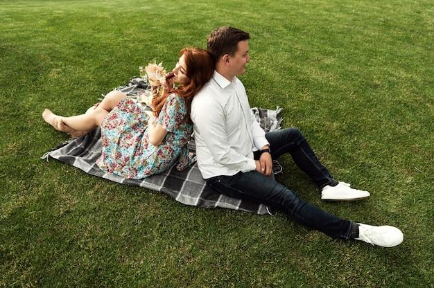 愛する素敵なカップルが公園でピクニックをし、ベッドカバーに花と食べ物が入った籐のバスケットを持っていました。幸せな恋人たちはピクニックで笑って食べます。ロマンチックなデート