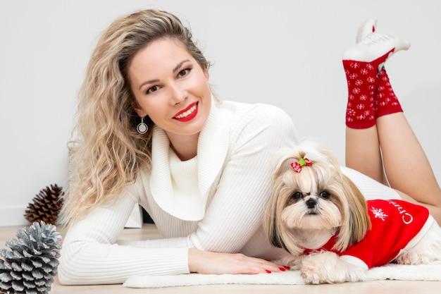 クリスマスのための手入れの行き届いた、素敵な服を着たシーズーの子犬を持つ素敵な女の子