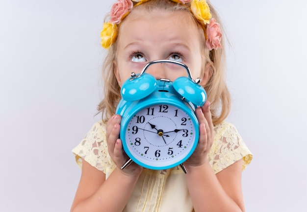 白い壁を見上げながら青い目覚まし時計を示す花のヘッドバンドで黄色のシャツを着ている素敵な女の子