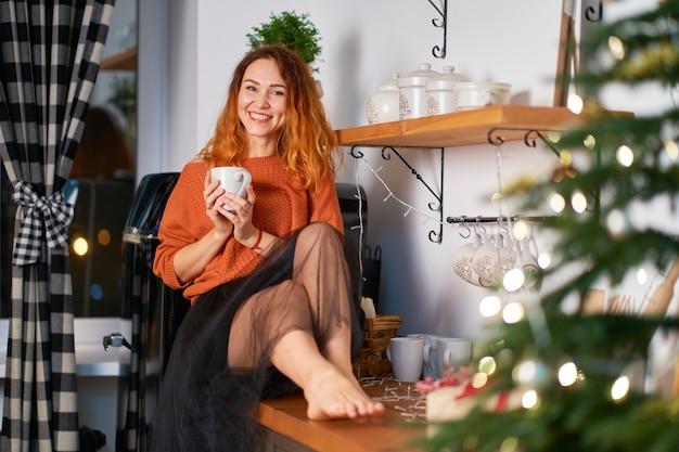 クリスマスのために装飾されたスタイリッシュで居心地の良いキッチンの屋根の布の上に素敵な赤毛の女の子が座っています