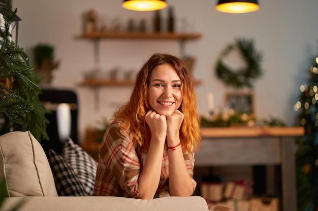 Милая рыжая девушка с загадочной улыбкой строит планы на новый год.
