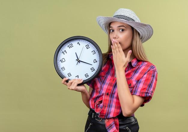 Милая молодая женщина в клетчатой рубашке в шляпе держит настенные часы, держа руку во рту на зеленой стене