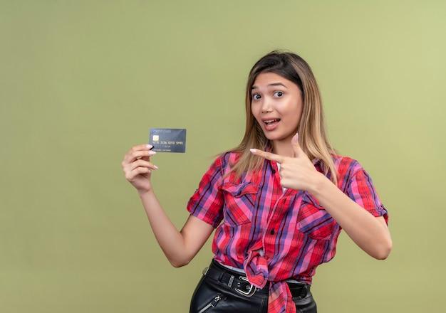 Милая молодая женщина в клетчатой рубашке показывает кредитную карту и показывает на нее указательным пальцем