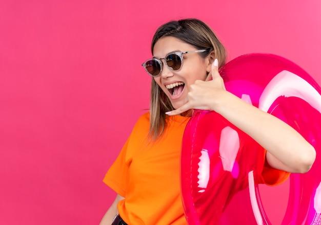 ピンクの壁にピンクのインフレータブルリングを持っている間、笑顔と見せるサングラスをかけているオレンジ色のtシャツを着た素敵な若い女性が私をジェスチャーと呼んでいます